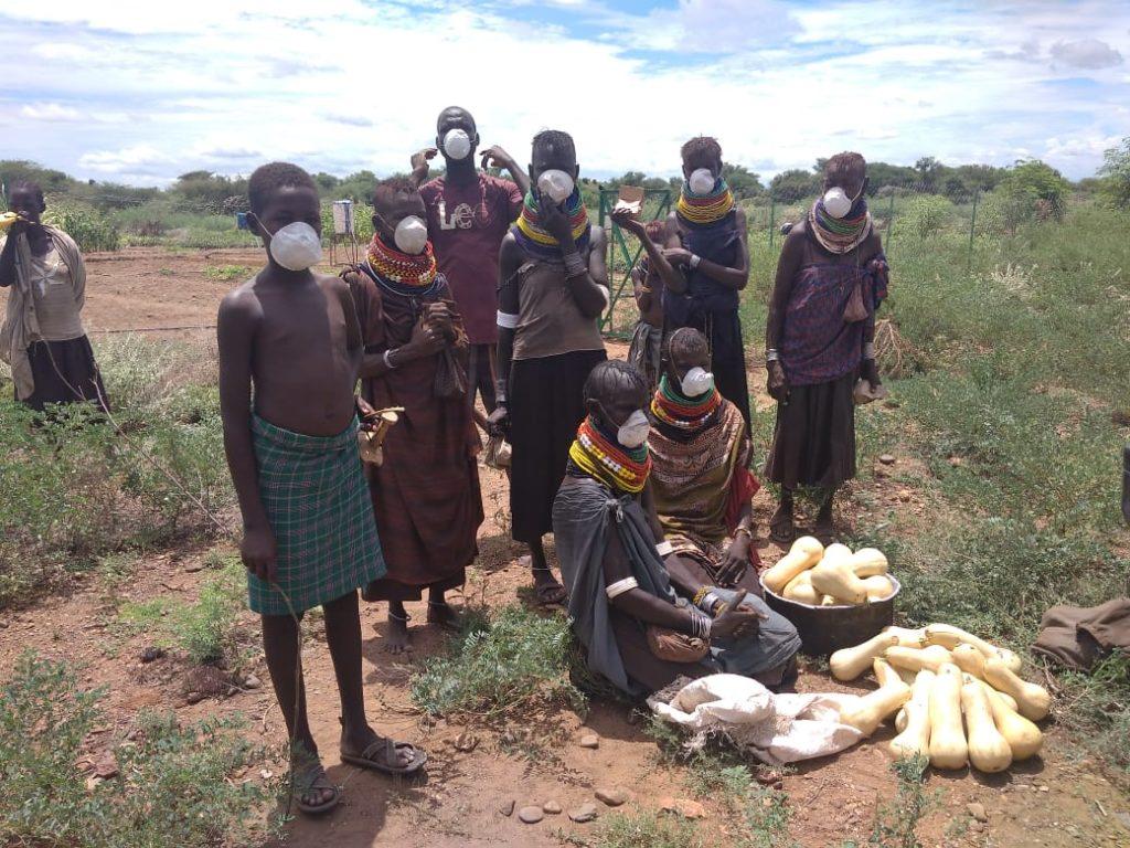 """Estudiantes del proyecto """"Furrows in the Desert"""" con mascarillas mientras realizan la recolección de los productos de la huerta"""